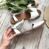 Άσπρα σανδάλια σε ένα ξύλινο υπόβαθρο στοκ φωτογραφία με δικαίωμα ελεύθερης χρήσης
