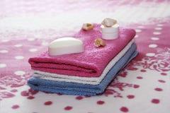 Άσπρα σαπούνι και ντεκόρ τουαλετών στα πλαίσια των ρόδινων πετσετών υφασμάτων στοκ φωτογραφία με δικαίωμα ελεύθερης χρήσης