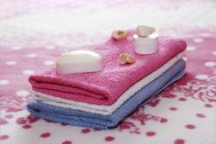 Άσπρα σαπούνι και ντεκόρ τουαλετών στα πλαίσια των ρόδινων πετσετών υφασμάτων στοκ φωτογραφίες