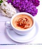 Άσπρα στρογγυλά φλυτζάνι και πιατάκι Cappuccino στον άσπρο πίνακα Στοκ Εικόνες