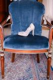 Άσπρα συμπαθητικά νυφικά παπούτσια στην μπλε καρέκλα Στοκ φωτογραφία με δικαίωμα ελεύθερης χρήσης