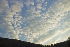Άσπρα σύννεφα στον ουρανό στο ηλιοβασίλεμα στα βουνά Στοκ εικόνα με δικαίωμα ελεύθερης χρήσης