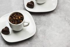 Άσπρα φλυτζάνια για το espresso που γεμίζουν με τα φασόλια καφέ και τη σοκολάτα ι Στοκ Εικόνες
