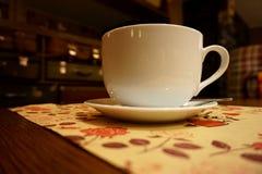 Άσπρα φλυτζάνι και πιατάκι σε έναν ξύλινο πίνακα σε έναν άνετο καφέ στοκ εικόνες με δικαίωμα ελεύθερης χρήσης