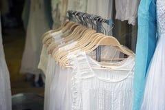 Άσπρα φορέματα στις κρεμάστρες Στοκ φωτογραφία με δικαίωμα ελεύθερης χρήσης