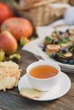 Άσπρα φλυτζάνι και πιατάκι με το τσάι και μπισκότα υπό μορφή φύλλου σφενδάμου σε έναν ξύλινο πίνακα Στοκ φωτογραφία με δικαίωμα ελεύθερης χρήσης