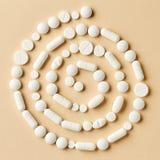 Άσπρα χάπια ιατρικής στο μπεζ υπόβαθρο Στοκ εικόνα με δικαίωμα ελεύθερης χρήσης