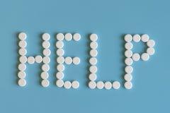 Άσπρα χάπια στην μπλε βοήθεια λέξης υποβάθρου Άσπρα ιατρικά χάπια σε ένα μπλε υπόβαθρο Έννοια λέξης βοήθειας Στοκ Φωτογραφία