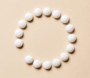 Άσπρα χάπια στο μπεζ υπόβαθρο Στοκ φωτογραφία με δικαίωμα ελεύθερης χρήσης