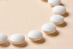 Άσπρα χάπια στο μπεζ υπόβαθρο Στοκ Φωτογραφίες