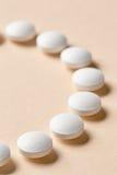 Άσπρα χάπια στο μπεζ υπόβαθρο Στοκ Εικόνες