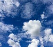 Άσπρα χνουδωτά σύννεφα ενάντια σε έναν βασιλικό μπλε ουρανό Στοκ Φωτογραφίες
