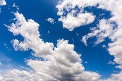 Άσπρα χνουδωτά σύννεφα στο μπλε ουρανό στην ηλιόλουστη ημέρα στοκ εικόνες