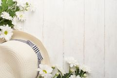 Άσπρα χρυσάνθεμα με ένα καπέλο σε ένα άσπρο ξύλινο υπόβαθρο, με ένα κενό διάστημα για το γράψιμο ή τη διαφήμιση στοκ εικόνα με δικαίωμα ελεύθερης χρήσης