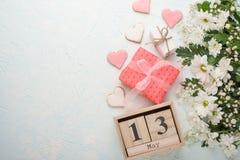 Άσπρα χρυσάνθεμα σε ένα ξύλινο υπόβαθρο με ένα ημερολόγιο στο οποίο στις 13 Μαΐου, το διεθνές Mother& x27 ημέρα του s στοκ εικόνες με δικαίωμα ελεύθερης χρήσης