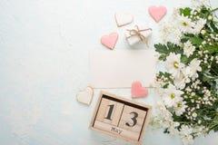 Άσπρα χρυσάνθεμα σε ένα ξύλινο υπόβαθρο με ένα ημερολόγιο στο οποίο στις 13 Μαΐου, το διεθνές Mother& x27 ημέρα του s στοκ εικόνα με δικαίωμα ελεύθερης χρήσης