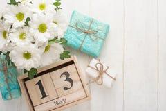 Άσπρα χρυσάνθεμα σε ένα ξύλινο υπόβαθρο με ένα ημερολόγιο στο οποίο στις 13 Μαΐου, το διεθνές Mother' ημέρα του s στοκ φωτογραφίες