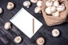 άσπρα champignon μανιτάρια στον ξύλινο μαύρο πίνακα με το boo σημειώσεων Στοκ Φωτογραφίες