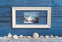 Άσπρα foto και κοχύλια πλαισίων whith σε ένα υπόβαθρο των μπλε πινάκων Στοκ Εικόνα