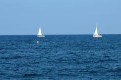 Άσπρα sailboats ή γιοτ σκαφών που επιπλέουν στη θάλασσα στοκ φωτογραφίες