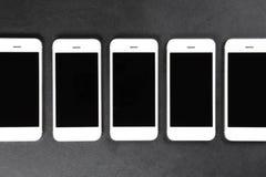 Άσπρα smartphones που βρίσκονται σε μια σειρά στη σκοτεινή επιφάνεια Στοκ Φωτογραφίες