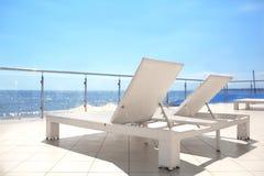 Άσπρα sunbeds στο πεζούλι ενός ακριβού ξενοδοχείου κοντά στην τροπική παραλία Πολλή άσπρη γέφυρα προεδρεύει κοντά στην παραλία θά στοκ φωτογραφία με δικαίωμα ελεύθερης χρήσης