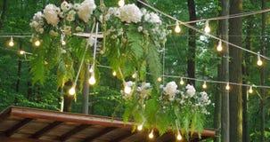 Άσπρες γαμήλιες καρέκλες με τα λουλούδια γάμος τελετής υπαίθρια Γαμήλια οργάνωση στον κήπο Στοκ Φωτογραφία