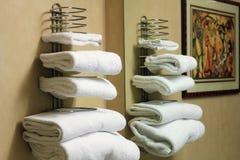 Άσπρες διπλωμένες πετσέτες λουτρών σε ένα ράφι Στοκ Εικόνες