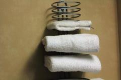 Άσπρες διπλωμένες πετσέτες λουτρών σε ένα ράφι Στοκ Εικόνα