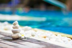 Άσπρες ισορροπημένες πέτρες και άσπρο plumeria πλησίον Στοκ φωτογραφία με δικαίωμα ελεύθερης χρήσης