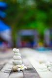 Άσπρες ισορροπημένες πέτρες και άσπρο plumeria πλησίον Στοκ Εικόνες
