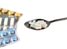 Άσπρες κάψες σε ένα κουτάλι, και άλλα χάπια στη φουσκάλα σε ένα λευκό Στοκ εικόνα με δικαίωμα ελεύθερης χρήσης