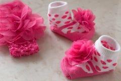 Άσπρες κάλτσες στα ρόδινα σημεία Πόλκα και ένα λουλούδι για το μωρό στο tabl Στοκ φωτογραφία με δικαίωμα ελεύθερης χρήσης