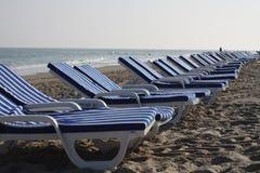 άσπρες και μπλε ριγωτές καρέκλες στην παραλία Στοκ Εικόνα
