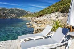 Άσπρες καρέκλες σαλονιών με τις ομπρέλες στην ακτή της διαφανούς θάλασσας Πολυτελής θέση για να μείνει στοκ φωτογραφία