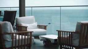 Άσπρες καρέκλες μαξιλαριών στην περιοχή σαλονιών θερέτρου πέρα από τα δέντρα με τη φυσική άποψη στον ωκεανό φιλμ μικρού μήκους