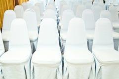 Άσπρες καρέκλες στην αίθουσα με το υπόβαθρο κουρτινών Στοκ Εικόνες