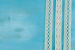 Άσπρες κορδέλλες δαντελλών στο μπλε ξύλινο υπόβαθρο Στοκ Εικόνες