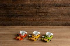 Άσπρες κούπες που κρατούν ψηλά για τον καφέ, σκοτεινό υπόβαθρο στοκ εικόνες