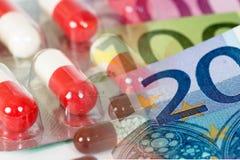 Άσπρες κόκκινες αντιβιοτικές κάψες με τα ευρο- τραπεζογραμμάτια στοκ φωτογραφία