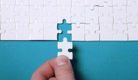 Άσπρες λεπτομέρειες ενός γρίφου στο πράσινο υπόβαθρο Ένας γρίφος είναι ένα puz Στοκ φωτογραφία με δικαίωμα ελεύθερης χρήσης