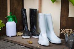 Άσπρες μπότες εργαλείων κηπουρικής και μαύρες μπότες Στοκ εικόνα με δικαίωμα ελεύθερης χρήσης