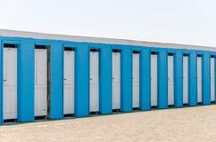 Άσπρες ξύλινες πόρτες σε ένα μπλε κτήριο για τα μεταβαλλόμενα ενδύματα στην παραλία Στοκ Εικόνες