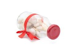 Άσπρες πέτρες στο διακοσμημένο μπουκάλι γυαλιού και το κόκκινο τόξο Στοκ φωτογραφίες με δικαίωμα ελεύθερης χρήσης