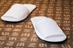 Άσπρες παντόφλες στο δωμάτιο ξενοδοχείου Στοκ εικόνα με δικαίωμα ελεύθερης χρήσης
