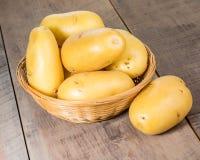 Άσπρες πατάτες φρέσκες που επιλέγει στο ψάθινο κύπελλο Στοκ Εικόνες