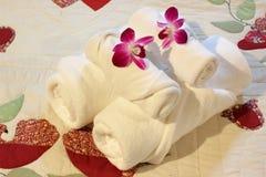 Άσπρες πετσέτες λουτρών στο κρεβάτι Στοκ Εικόνες