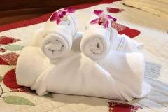 Άσπρες πετσέτες λουτρών στο κρεβάτι Στοκ φωτογραφία με δικαίωμα ελεύθερης χρήσης