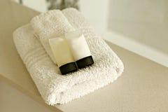 Άσπρες πετσέτες με το σαμπουάν και το εδαφοβελτιωτικό Στοκ Εικόνες