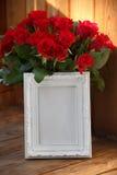 Άσπρες πλαίσιο και δέσμη των κόκκινων τριαντάφυλλων Στοκ εικόνα με δικαίωμα ελεύθερης χρήσης